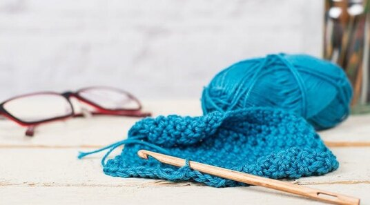 wooden crochet hook and blue yarn on a table