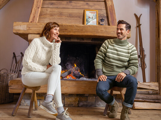 a man and woman in chunky knitwear by a fire