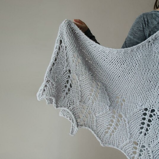 A person holding up a grey-coloured chunky weight lace knitting shawl