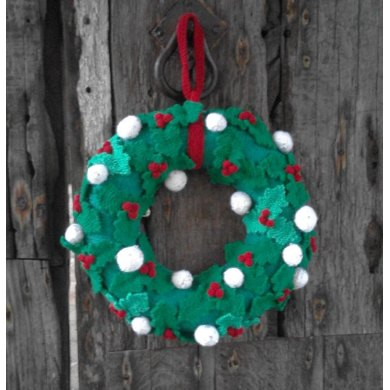 Knitted Christmas wreath with holly leaves, berries and snowballs