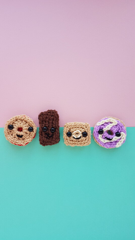 Four crocheted amigurumi biscuits in a row on a pink and blue background
