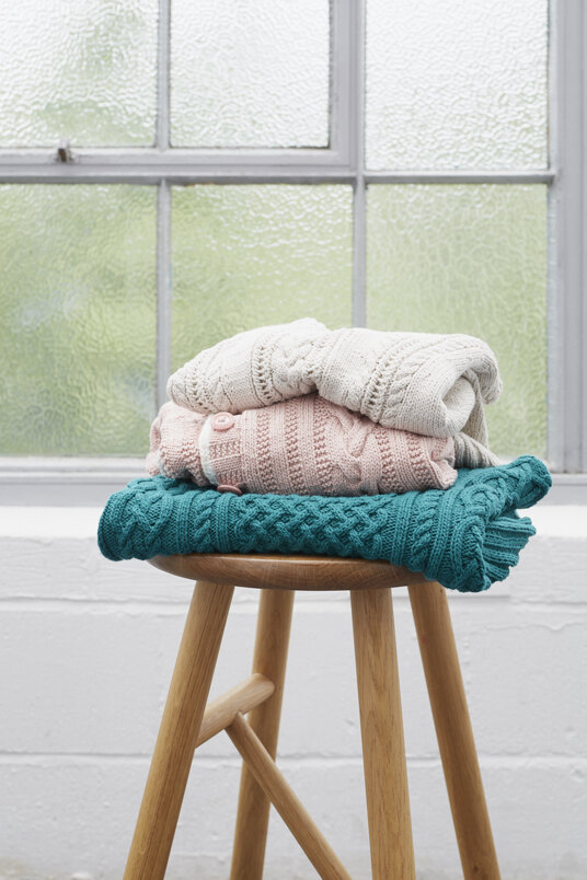 3 jumpers folded and stacked on top of one another, sitting on a stool