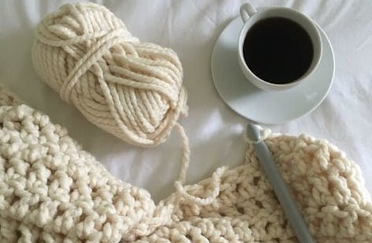 white yarn and half made crochet pattern on the bed