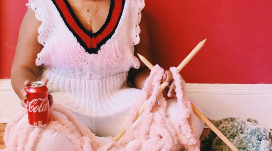 woman sat with yarn and a drink