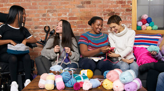 group of people laughing and knitting together