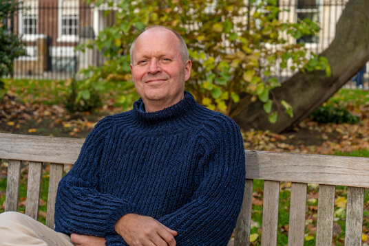Man wearing navy jumper knitted with fisherman's rib stitch