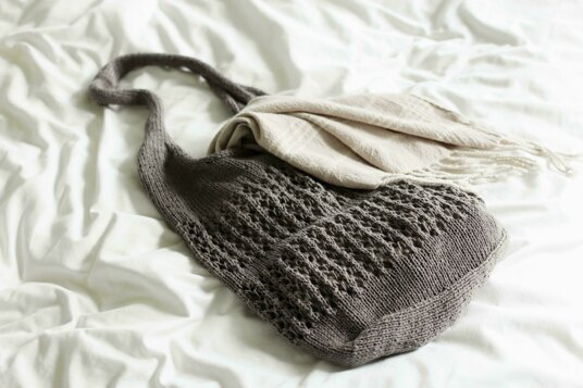 A grey knitted bag on a bed, with a scarf hanging out the top