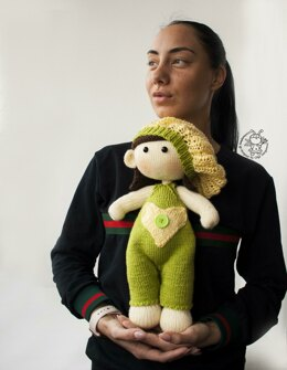 Baby doll in green overalls knitting flat