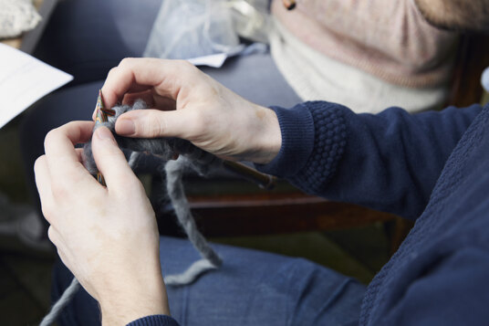 A person's hands knitting with dark grey coloured yarn