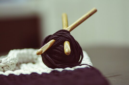A chunky ball of yarn with two crochet hooks