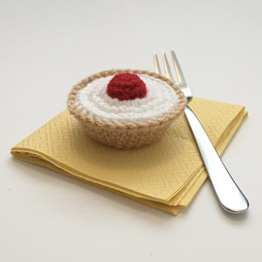 crocheted cherry bakewell tart with a fork
