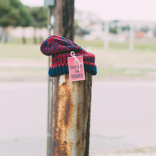 A hat with a tag that says 'take me I'm yours' on it, outside on a wooden post
